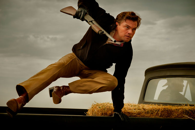 Leonardo DiCaprio hyppää auton konepellin yli.