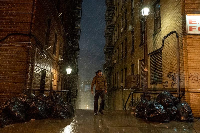 Mies kävelee vesisateessa.