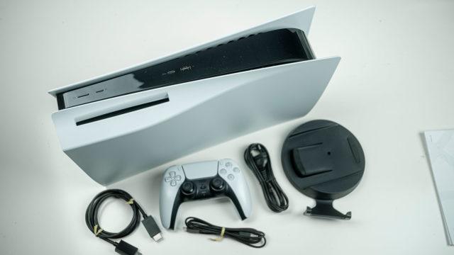 PS5-pakkauksen sisältö levitettynä pöydälle.